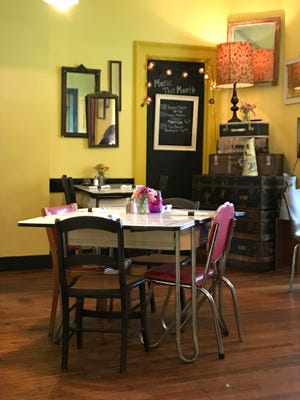 The first floor of Roots Cafe has brightly painted yellow walls.