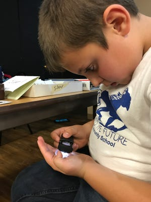 Owen Ritten studies a 1964 quarter at the Mid Minnesota Coin Expo in St. Cloud on Sunday, Oct. 8.