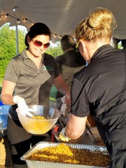 Chef April Boeke of Culinary Innovations serves fresh sweet corn at this summer's Seton Harvest twilight dinner.