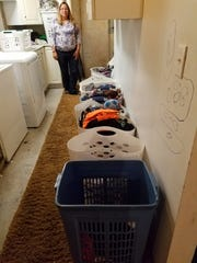Once the children are in sixth grade they learn how to do their own laundry. Lori  O'Brien shows off the wash room in the basement.