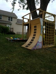 "The O'Brien clan loves the ""Ninja Warrior"" TV show, so Dan made a warped wall on the swing set the kids helped to build. On the other side of the swing set are the kids' painted handprints."