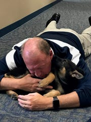 Siegel High principal Larry Creasy plays with the school's newest mascot Nova after school earlier this week.