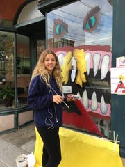 Evelyn Martinez, a North Rockland 12th grade art student, paints a business window.