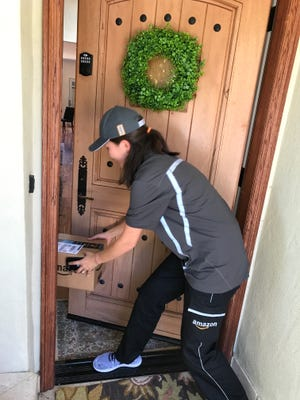 An Amazon Logistics delivery person places a package inside the front door of a customer after having the smart lock on the door opened by the Amazon Key system.