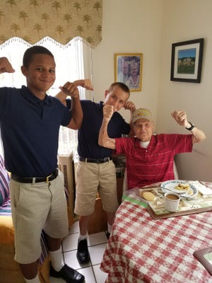 Andre and Isaac, Samaritan Center for Young Boys & Families students, spend time with 106-year-old Meals on Wheels recipient, Mr. Howard.