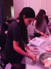 Elana Bohm, 16, of Colts Neck braids the challah dough
