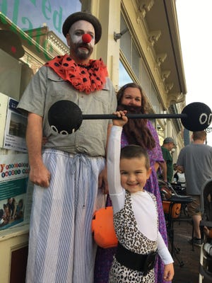 Joe, Carissa and 4-year-old Charlie Engel, of Staunton, dressed as a clown, bearded lady and strong man, pose for a photo during the Halloween downtown trick-or-treating event in Staunton, Va., on Saturday, Oct. 28, 2017.