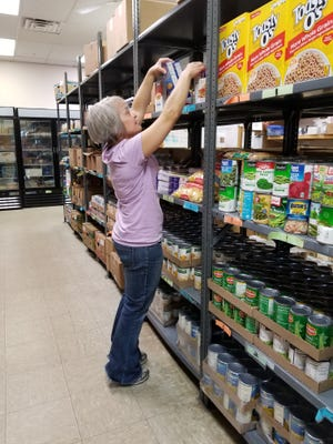 Volunteer Cindy Etringer stocks shelves at the St. Vincent de Paul food pantry, 169 North Central Avenue, in downtown Marshfield.