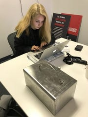 Team Kasie member Ava Edwardson works on a laptop Saturday with a prototype of a hot and cold lunchbox in the foreground. Edwardson, a sophomore at Enterprise High School, contributed a brand and logo for the product idea by 8-year-old Kasie Johnson.
