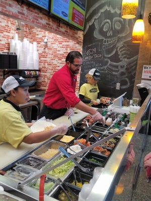 Owner Eduardo Ruiz helps customers with their choices of freshly made salsas and toppings at the Taqueria Company.