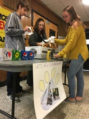 Members of Gloucester High School's Leo Club - senior Rick Gaskill, 17, (left), media center specialist Rachel Donohue and junior Emily Petrik, 17 - are collecting change and selling pretzels after school for Luis Chiclana, a boy from Puerto Rico staying at Ronald McDonald House of Southern New Jersey for medical treatment. Club members read about Luis in the Courier Post and wanted to help his family.