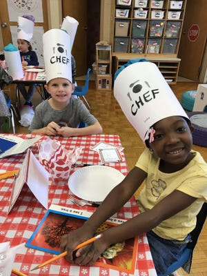 "Kindergarten students Uriah Thompson, left, and India Smart participate in a ""book tasting"" event at Coolidge Elementary School, Neenah. Students took a ""field trip"" to the country of Italy. They explored a variety of topics while in the setting of an Italian restaurant."