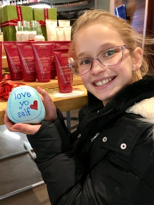 """Hayden Ames holds up a rock that says """"love yo self"""" that the girls placed at Neroli Salon and Spa Brookfield."""