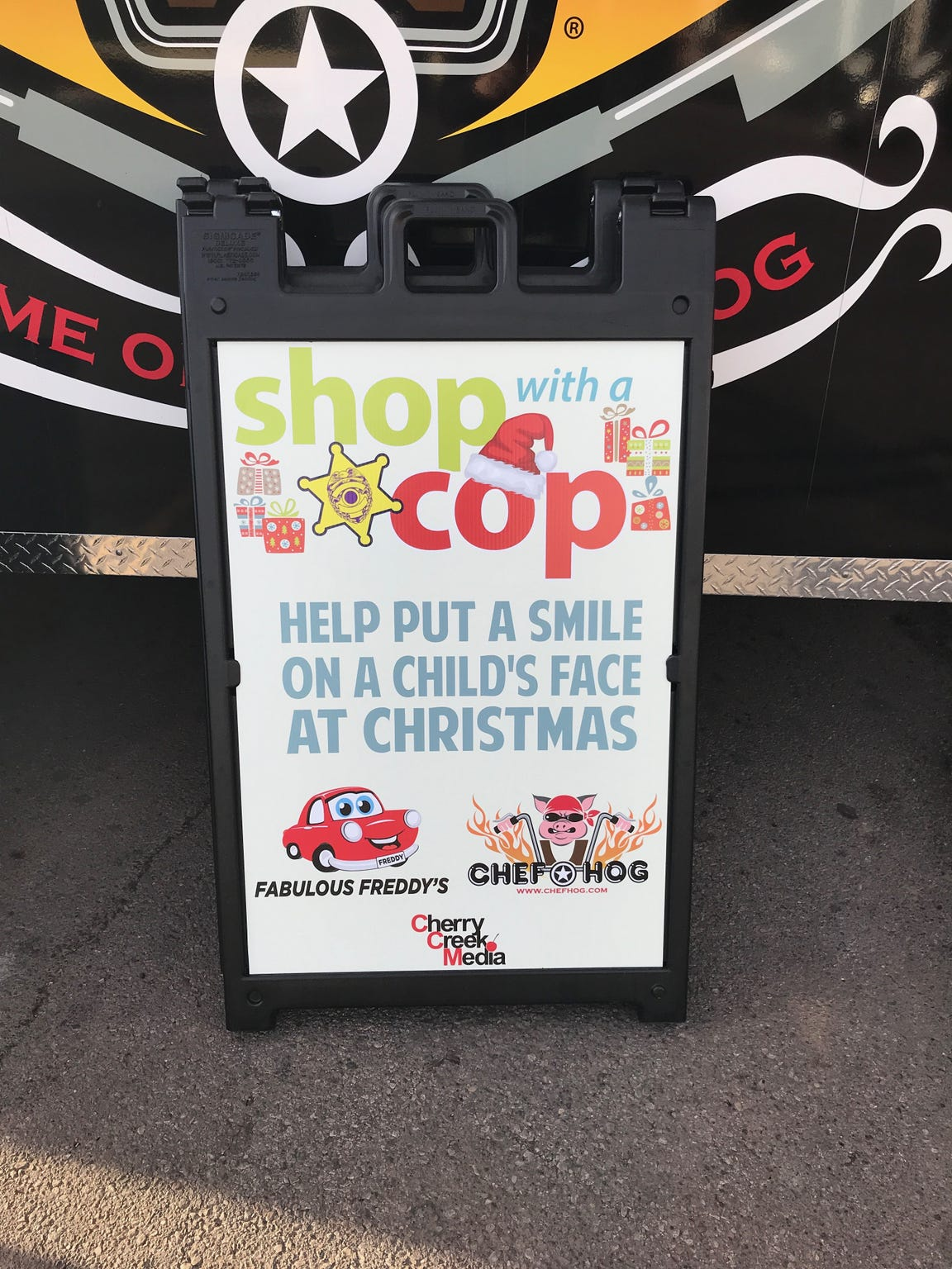 A Shop With a Cop sign stands outside the Chef Hog