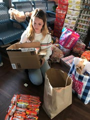 Sophomore Emily Brewer packs away some of the 10,000 canned goods donated in the drive.