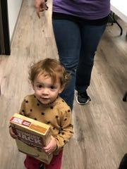 Seventeen-month-old Lizzie O'Dea helps mom Kristen O'Dea load the food.