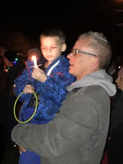 Jack Kindseth holds his son, Levi, while listening to Christmas carols at the Gov. Warner Mansion.