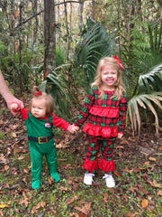 Sisters Marie and Avery Guidry wear Christmas pajamas for their first state park visit of December. They stand in front of dwarf palmettos, the namesake of Palmetto Island State Park.