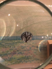 Tiny art by Leigh Anna Newell is seen through a magnifying