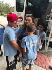 Bruce Rogers, Mrs. Candice Hawes, Landon Ward and Tristan Smith load food boxes onto the truck.