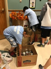 Landon Ward loads up a box of donations during the