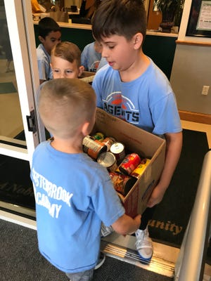 Teamwork in motion: Waylen Jewett, Chad Hinkle and Jace MacLane help each other carry the donations.