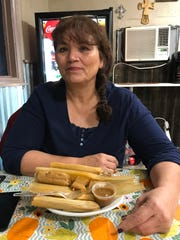 Mary Martinez, owner of Maria's Tamaleria, sits with a plate of tamales.