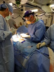 Lt. Col. Eric Ahnfeldt, center in purple cap, performs surgery during his deployment in Puerto Rico.