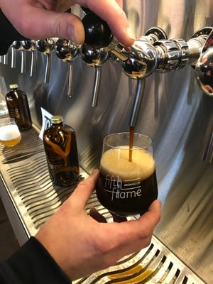 Brewer Jon Mervine pours a sample of Parlance of our Times, an oatmeal stout, at Fifth Frame Brewing on St. Paul Street in Rochester Wednesday.