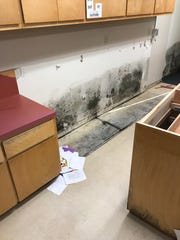 After flooding at an Orangefield school, mold could be found behind countertops. Damage like this forced classes to meet in sections of the school gym or other areas like custodial closets.
