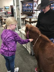 Mary Coffey holds the rope while a young customer at