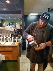 David Rudibaugh pours a latte at White Swan Coffee
