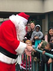 Santa greets students during a Christmas party at C.A.