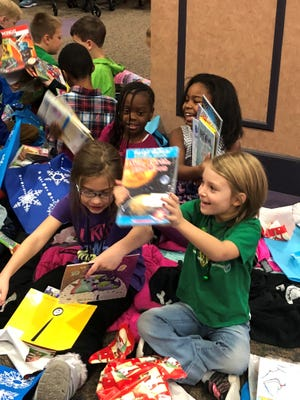 A group of first graders excited about their new books.
