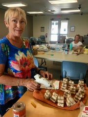 Volunteer Jacque Morton prepares Winter Green Night Lights crafts. More than300 visitors attended the annual event in early December.