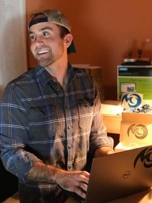 "Pinckney native Jeff Cremonte works in his ""office,"" which is a section of his bedroom in Durham, NC. The 24-year-old founded a small business Michigan Overboard and will donate 21% of his profits to organizations working to protect the Great Lakes."