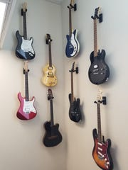 a collection of old, electric guitars were hung on