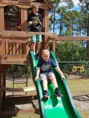 Thanks to the generosity of the community, Cody Brimley (on slide) and Liam Wright enjoy hours on their special playground.