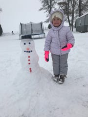 Isabell Fields builds a snowman.