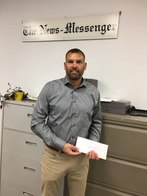 Scott Lang of the Fremont Club accepts a check from the Gannett Foundation to be used for literacy programs in Sandusky County.