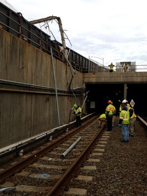 PATCO Hi-speedline workers assess damage and repair requirements from an accident Monday east of the PATCO tunnel and below the Conrail line in Camden. Both trains hit the same utility pole, disrupting passenger service that remains reduced through Wednesday