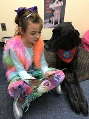 At Webster's Schlegel Elementary School, Payton listens attentively as Lily Rivera reads her a book. Payton visits the school once a week.