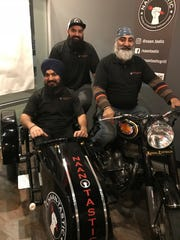 Ajay, Aman and Mandeep Singh pose on a Royal Enfield motorcyle on display in their restaurant, Naan-Tastic.