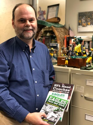 Author John Maxymuk poses with the books he's written on the Eagles and NFL head coaches.