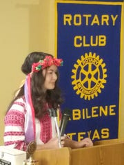 Dressed in traditional holiday garb, Elizabeth Kim speaks to members of the Rotary Club of Abilene about life in rural Ukraine.