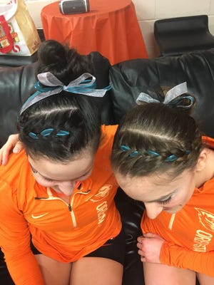 Oregon State gymnasts Mariana Colussi-Pelaez (left) and Mary Jacobsen display teal ribbons the team is wearing to support sexual assault survivors.