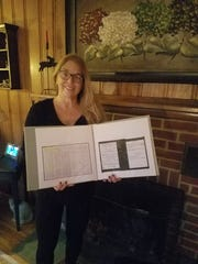 Lenape High School teacher Kate DeSantis holds up a scrap book, which was put together for her by Shawnee student Eric Schubert, who runs ES Genealogy. Schubert took about a  day to find out detailed information about the birth family of DeSantis, who was adopted as an infant.