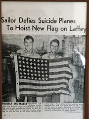 Bill Kelly (left) holds the Laffey's tattered American
