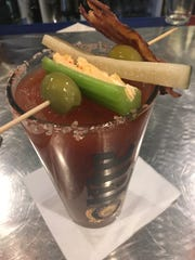 This classic Bloody Mary ($8) at Vespa Kitchen is delicious and served with celery stuffed with pimento cheese, candied bacon, an olive, and housemade pickle. The Bloody Mary mix is made in house and is mixed with Tito's vodka.