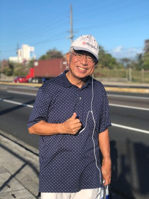 Sammy Hiro, 70, takes his morning walk along Route 1 Marine Corps Drive every day armed with a pair of tongs and a plastic bag, picking up trash he sees along the way. Hiro said picking up trash is just a small way to show his appreciation for the island.